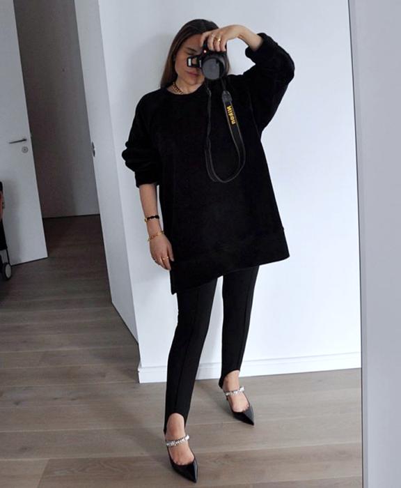 chica de cabello castaño largo usando un suéter negro oversized, leggings negros de estribos, zapatos negros de tacón con correas con brillantes