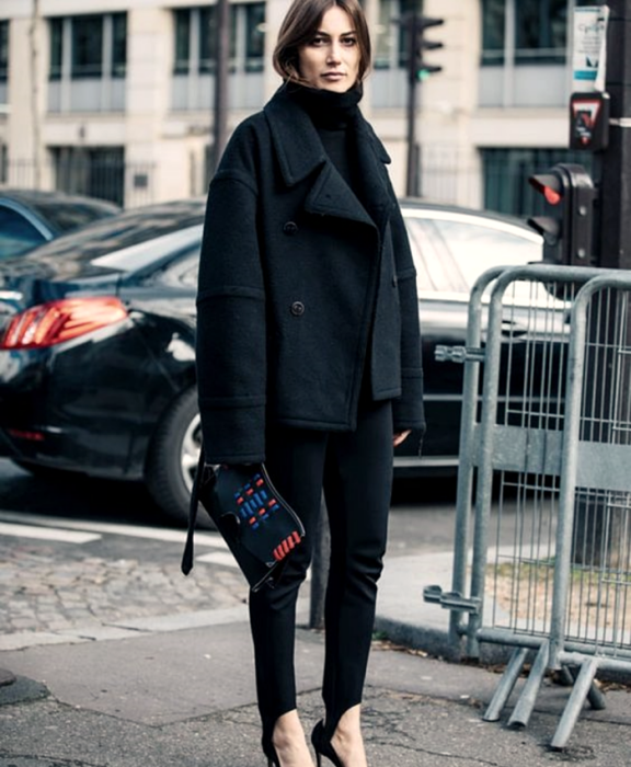 chica de cabello castaño usando un suéter de cuelo alto negro, abrigo grande negro, leggings con estribos negros, zapatos de tacón y bolso de mano negro con vistas rojas y azules