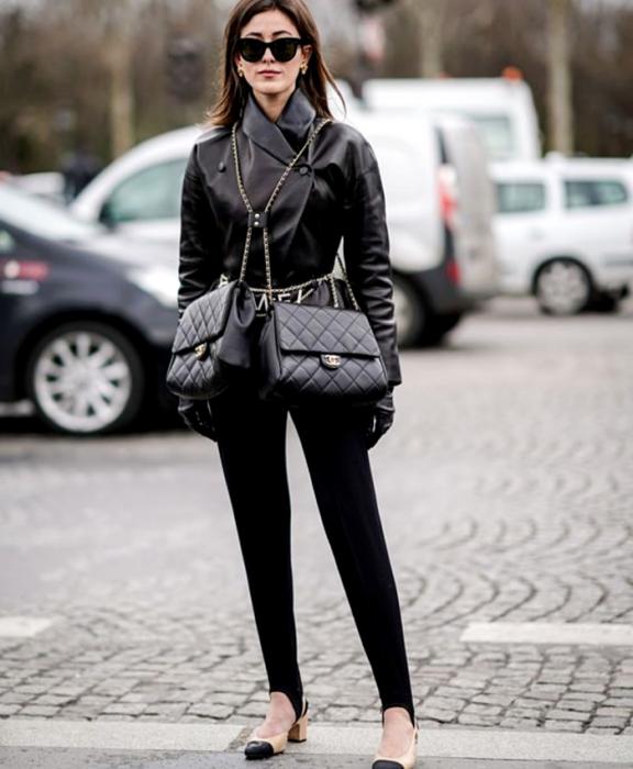 chica de cabello castaño usando lentes de sol, abrigo de cuero, bolso negro de correa de cadena, leggings negros con estribos y zapatos de tacón beige con puntas negras