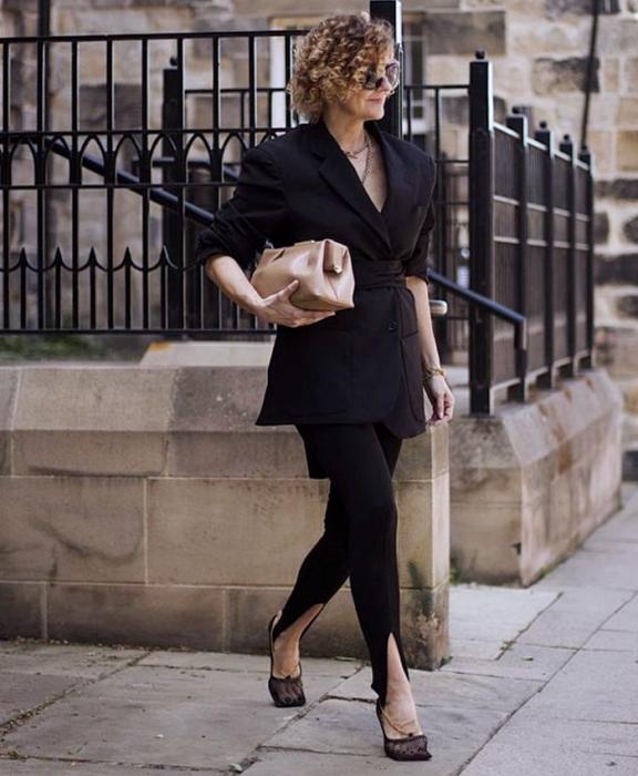 chica de cabello chino rubio usando lentes de sol, blazer oversized negro, leggings negros con estribos y zapatos de tacón semitransparentes, bolso de mano beige