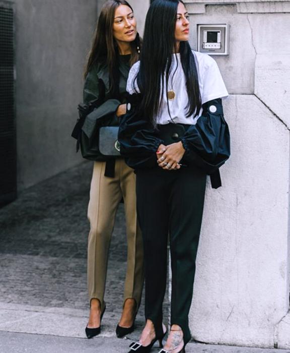 dos chicas de cabello largo usando una camiseta blanca, top negro, leggings negros y cafés con estribos, zapatos de tacón negro, chaqueta negra y bolso negro de mano