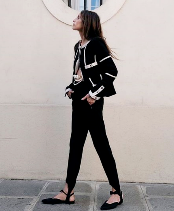 chica de cabello largo usando un top negro, cárdigan negro con vistas blancas, leggings con estribos negros, flats negros