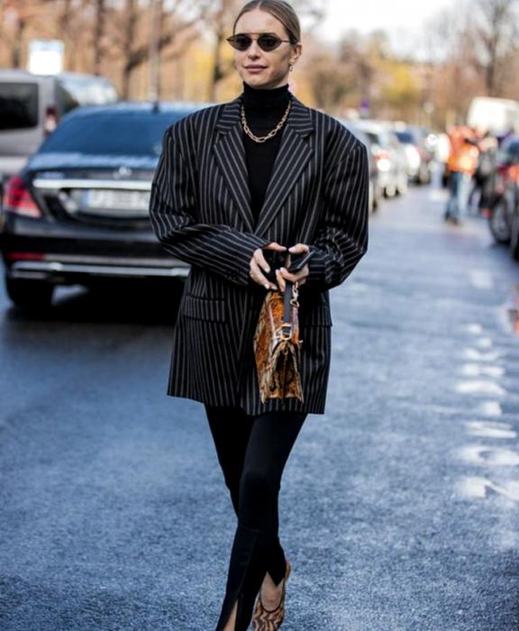 chica rubia con lentes de sol, top negro de cuello alto, blazer oversized negro de líneas negras, leggings negros con estribos, sandalias de tacón negras, bolso de mano café con animal print