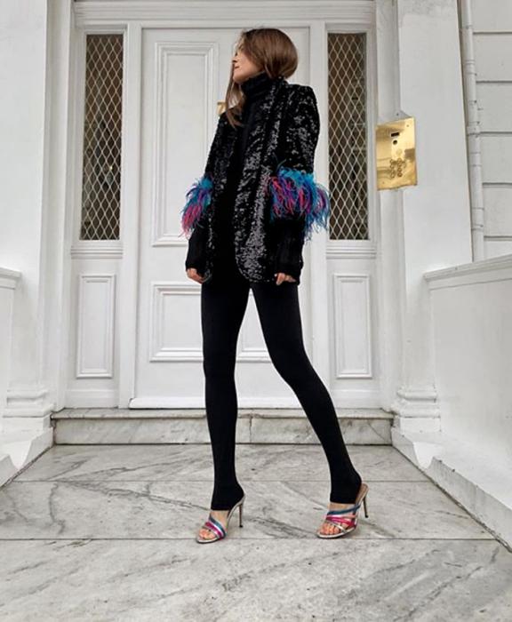 chica de cabello claro usando un top negro de cuello alto, blazer negro de brillantina con plumas azules y rosas en las mangas, leggings negros con estribos y sandalias de tacón de colores