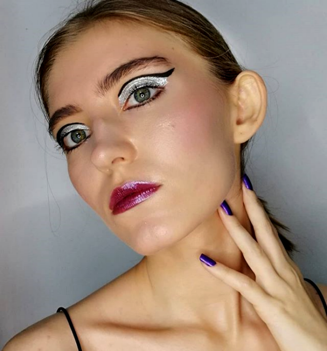 blonde girl with retro, vintage style makeup with silver glitter eyeshadow, graphic black thick liner and purple glossy lipstick