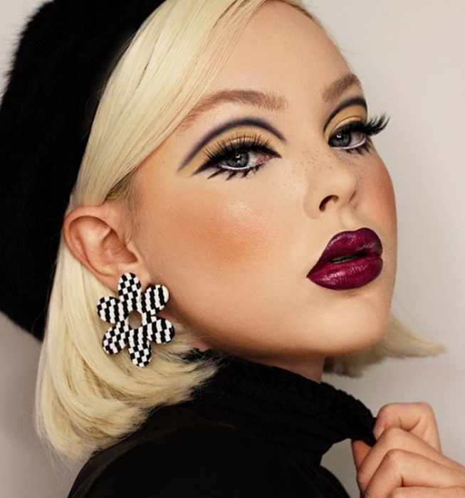 blonde girl wearing vintage style makeup, retro 60s and 70s style with thick graphic black outline, yellow shadows and false eyelashes, intense icing lipstick with black outline and gloss