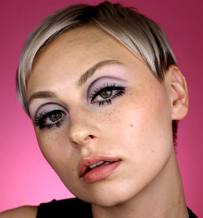 platinum blonde girl with vintage retro 60s and 70s makeup with lilac and white shadows, graphic thick black liner and false eyelashes