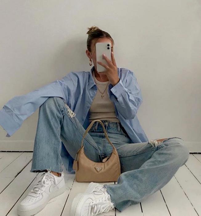 chica rubia usando un top beige, camisa de vestir azul celeste, jeans a la cintura, tenis blancos y bolso de mano beige