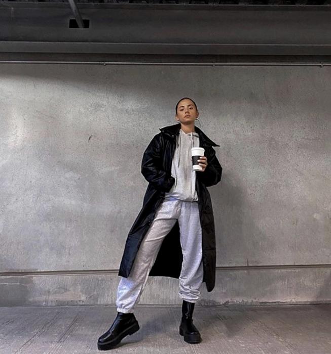 chica de cabello castaño usando una sudadera gris, pants grises, abrigo largo de cuero negro, botas de cuero de suela gruesa
