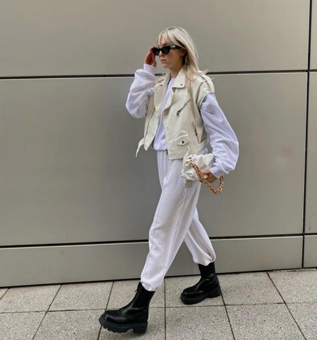 Platinum blonde girl wearing sunglasses, white sweatshirt, white denim vest, white pants, black chunky soled boots and beige handbag