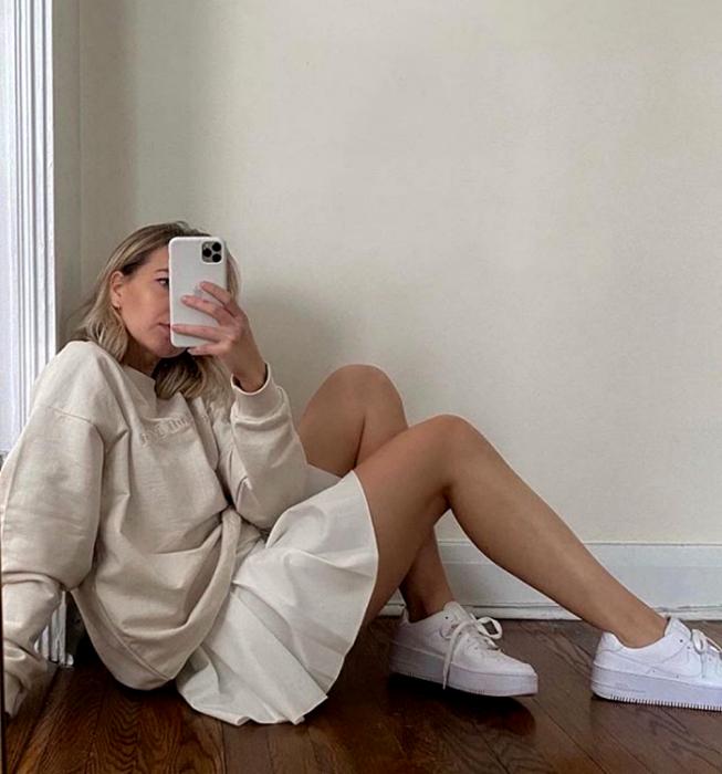 chica rubia usando sudadera oversized beige, falda blanca de tablones, tenis blancos