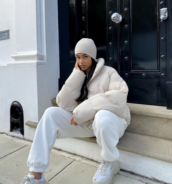 brunette girl wearing a beige beine hat, beige puff jacket, white pants, white sports sneakers