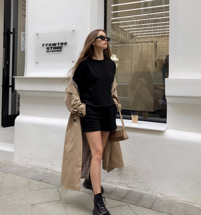 blonde girl wearing sunglasses, black t-shirt, black shorts, beige coat, thick-soled boots and beige leather mini bag