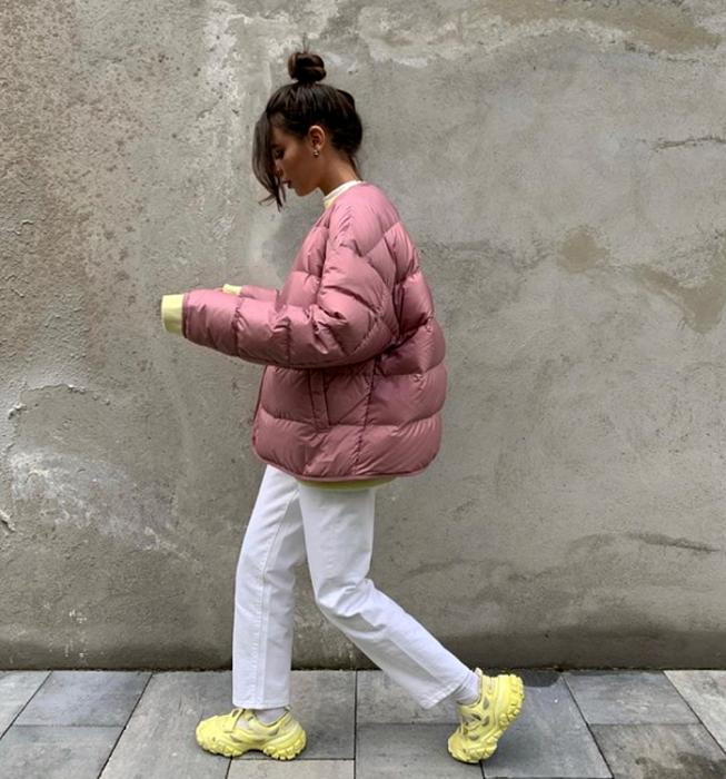 chica de cabello castaño usando una chamarra rosa puffer jacket, jeans blancos, tenis amarillos neón y sudadera blanca