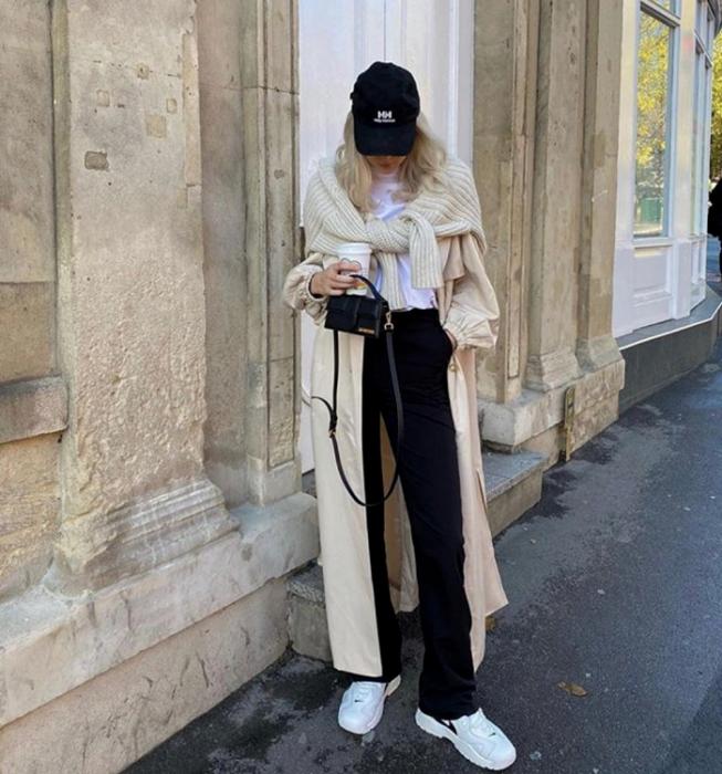 chica rubia usando gorra negra, camiseta blanca, pants negros, tenis blancos, abrigo largo beige, suéter beige tejido y bolso de mano mini negro