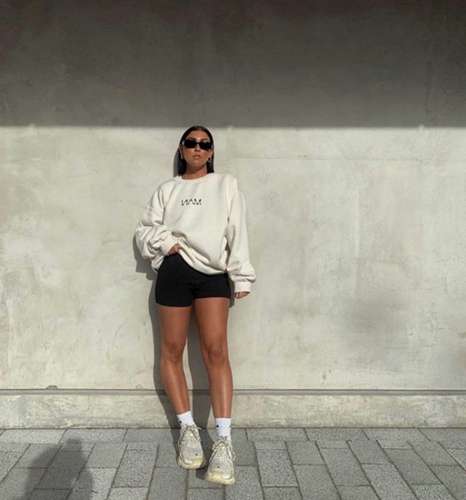 brown haired girl wearing sunglasses, white sweatshirt, black cycling shorts, white tennis shoes