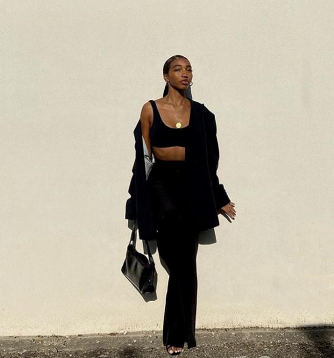chica morena usando un crop top negro, blazer negro oversized, pantalones de vestir negros, sandalias negras de tacón y bolso de mano negro