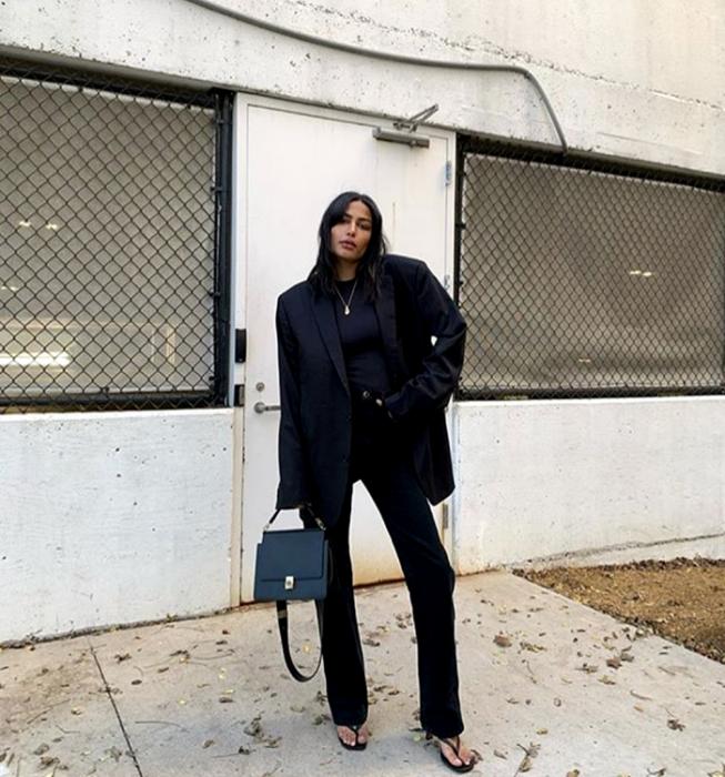 chica de cabello oscuro usando un top negro, blazer oversized negro, pantalones de vestir negros, sandalias de tacón negras, bolso de mano negro