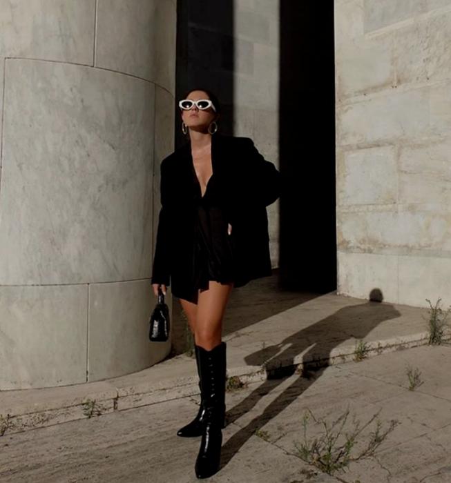 chica de cabello negro usando lentes de sol blancos, blazer negro oversized, vestido mini negro con escote en V, botas largas de cuero negras, bolso mini de cuero negro