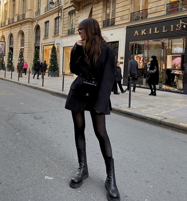 brown haired girl wearing sunglasses, oversized black blazer, black tights, black platform ankle boots, mini black leather tote bag