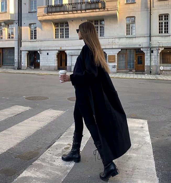 chica rubia usando lentes de sol, abrigo largo negro, skinny jeans negros, botines negros de plataforma y top  negro de cuello alto
