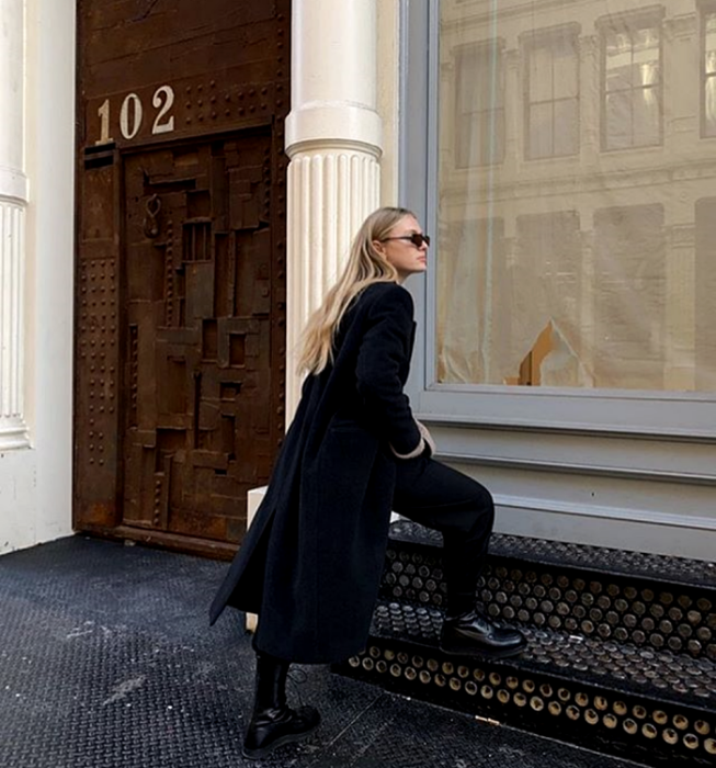 blonde girl wearing sunglasses, long black coat, black dress pants, thick-soled black ankle boots