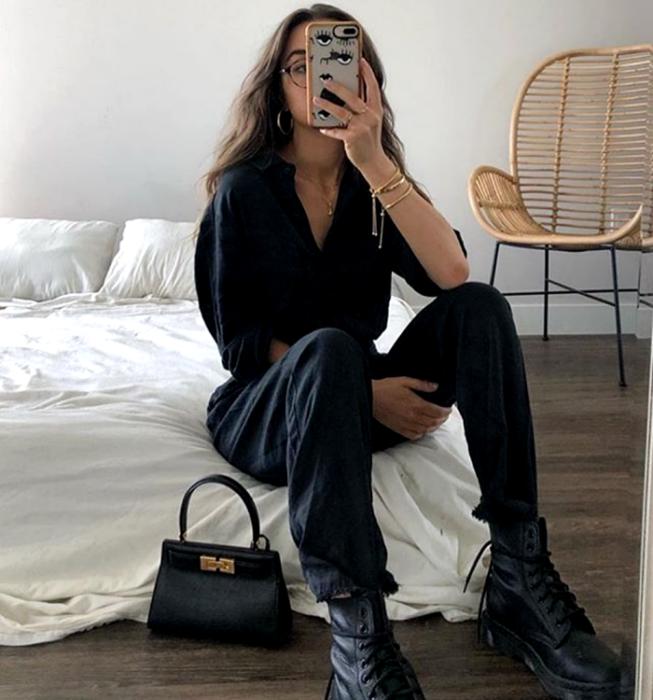 chica de cabello claro usando lentes, camisa de vestir negra, pantalones negros holgados, botines negros de suela gruesa, bolso de mano negro