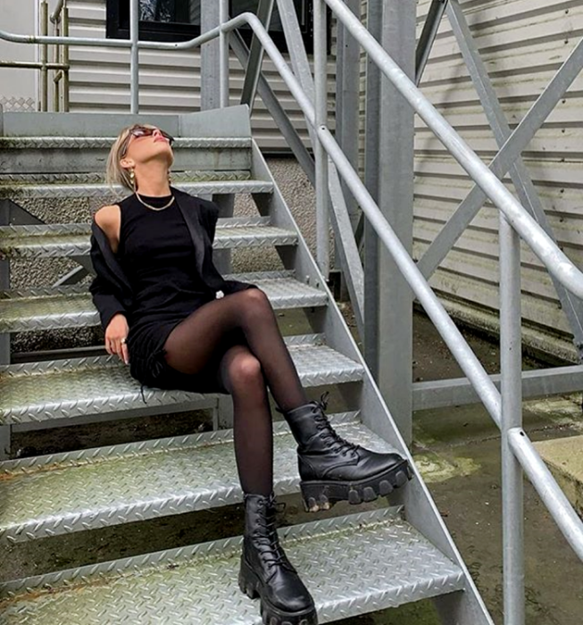blonde girl wearing sunglasses, short black sleeveless dress, black blazer, black semitransparent tights, black leather platform boots and thick sole