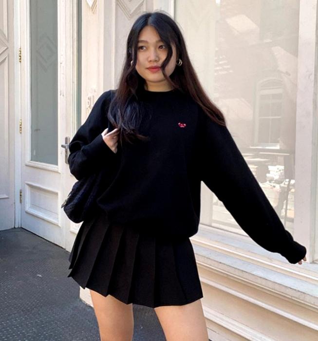 long haired girl wearing black sweatshirt, black plank mini skirt and black tote bag