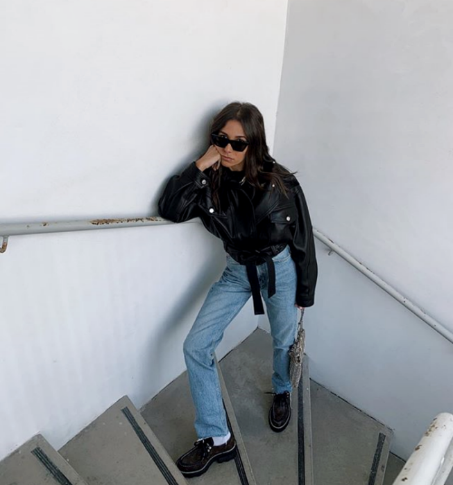 brown haired girl wearing sunglasses, black top, leather jacket, straight waisted jeans, black loafers and beige handbag