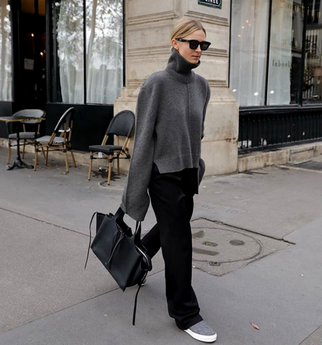 blonde girl with sunglasses, gray turtleneck sweater with baggy sleeves, black dress pants, gray tennis shoes and large black handbag