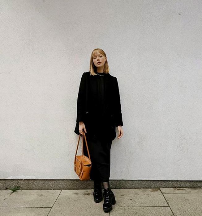 blonde girl wearing a black top, long black jacket, black dress pants, semitransparent black stockings, black heeled ankle boots and brown tote bag