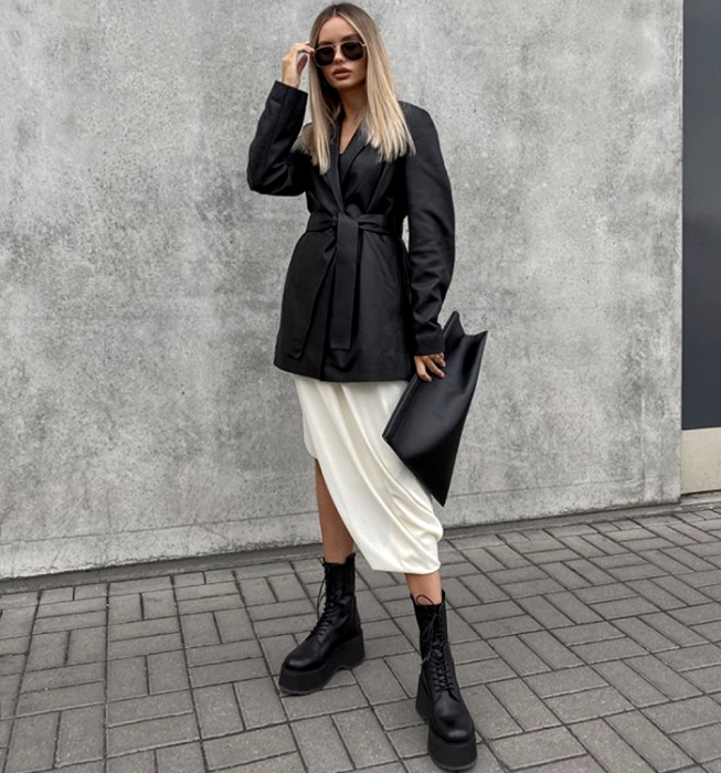 blonde girl with sunglasses, belted leather blazer jacket, white satin skirt, thick-soled black ankle boots and black clutch handbag