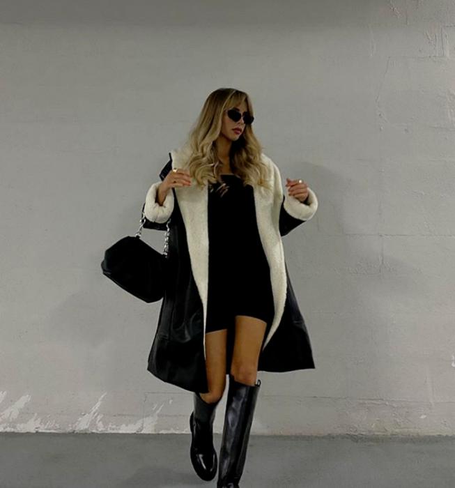 blonde girl with sunglasses, black mini dress, black coat with white plush lining, black long boots and black handbag