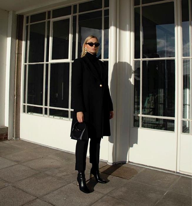 blonde girl with sunglasses, long black coat, black turtleneck sweater, black dress pants, black high heel ankle boots and black handbag