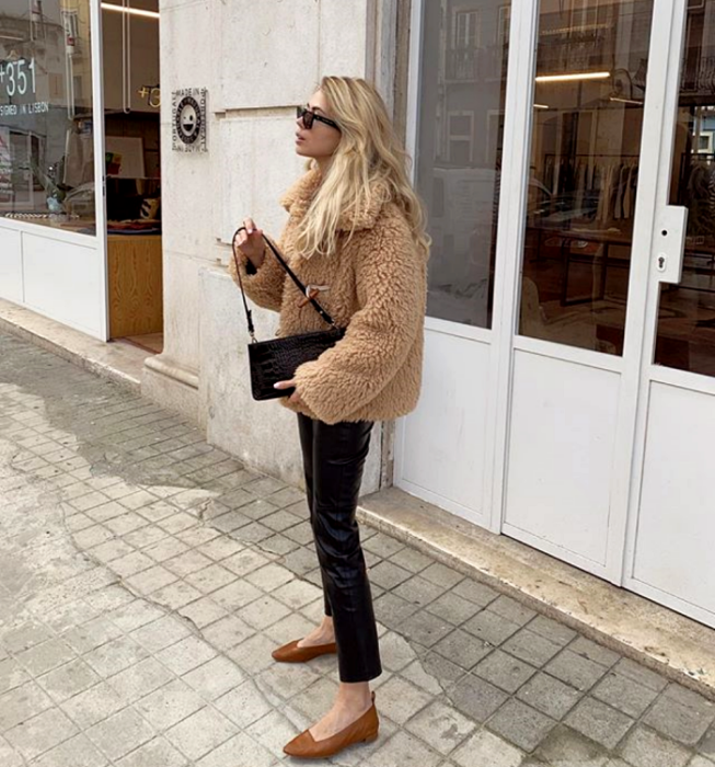 blonde girl wearing sunglasses, light brown teddy coat, leather pants, black leather handbag and brown flats