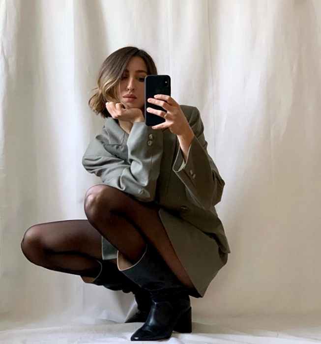 short hair girl wearing gray oversized blazer, black tights and long black heeled boots