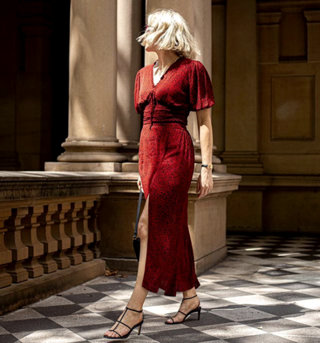 blonde girl wearing a long red dress with short sleeves, V-neckline and leg opening, with black high-heeled sandals
