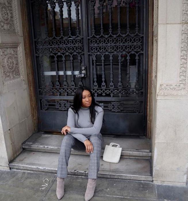 chica morena de cabello largo usando un suéter gris de cuello alto, pantalones grises de vestir con cuadros, botines grises de terciopelo y bolso mini de mano blanco