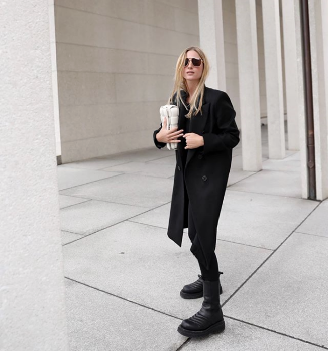 blonde girl wearing sunglasses, long black coat, black top, black leggings, black platform boots and beige handbag