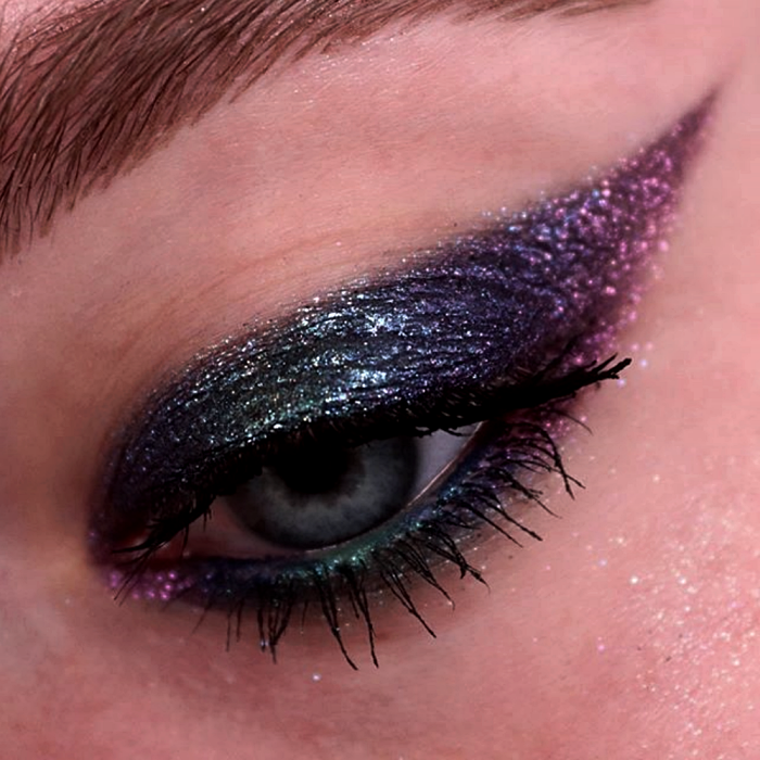 eye makeup with blue, purple, green and turquoise shadows with pink and blue glitter and black mascara