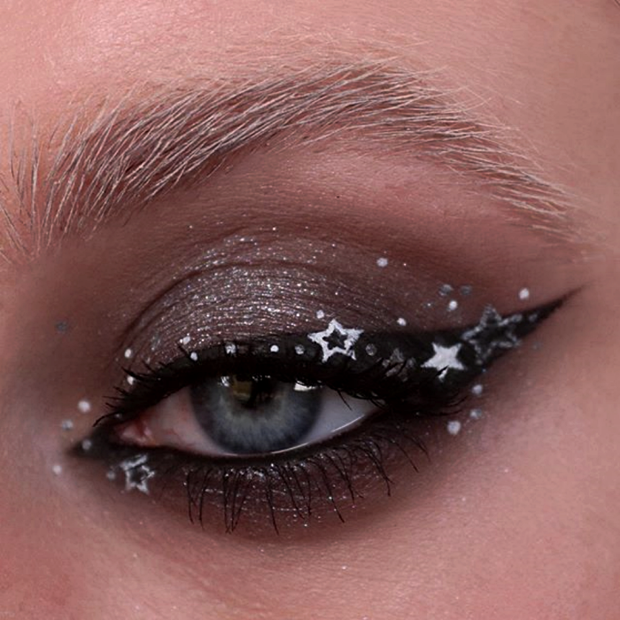 eye makeup with gray shadow, black cat-eye liner, and silver star graphic liner