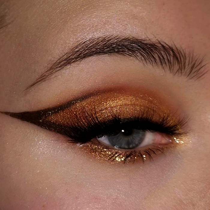 eye makeup with gold, yellow, brown shadows and graphic brown outline