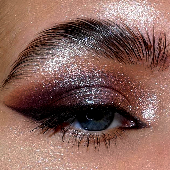 eye makeup with cherry, brown and purple shadows, shimmering glitter and dramatic black outlines