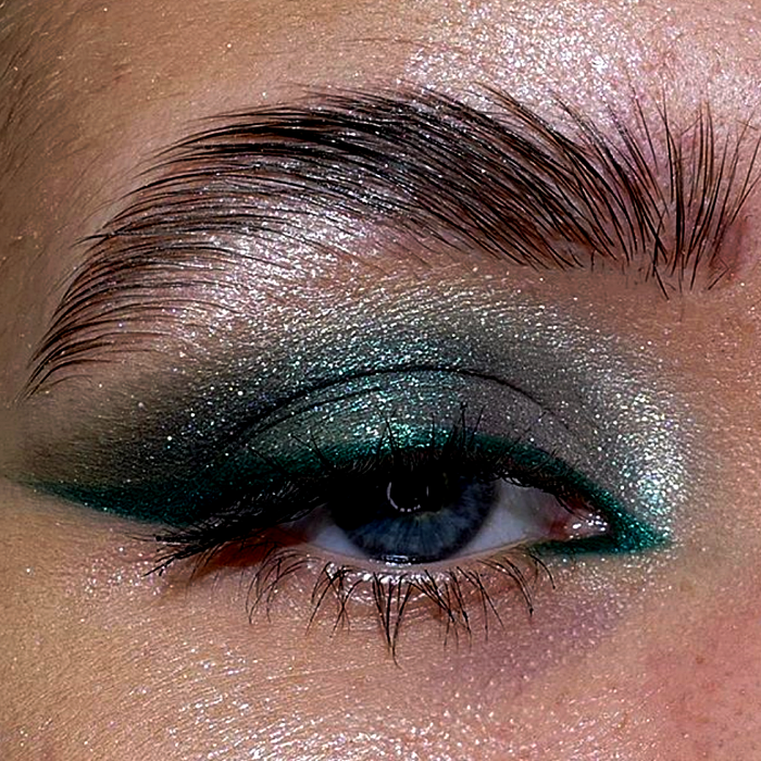 eye makeup with blue and light blue shadows, turquoise outlines and silver and gold glitter
