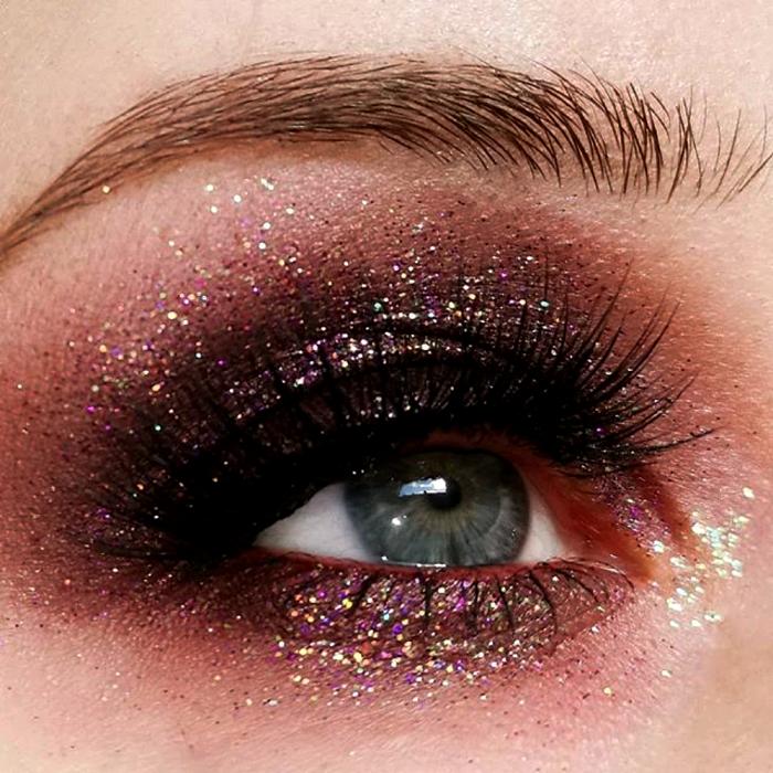 maquillaje de ojos con sombras guindas, cafés y negra, glitter rosa y pestañas postizas