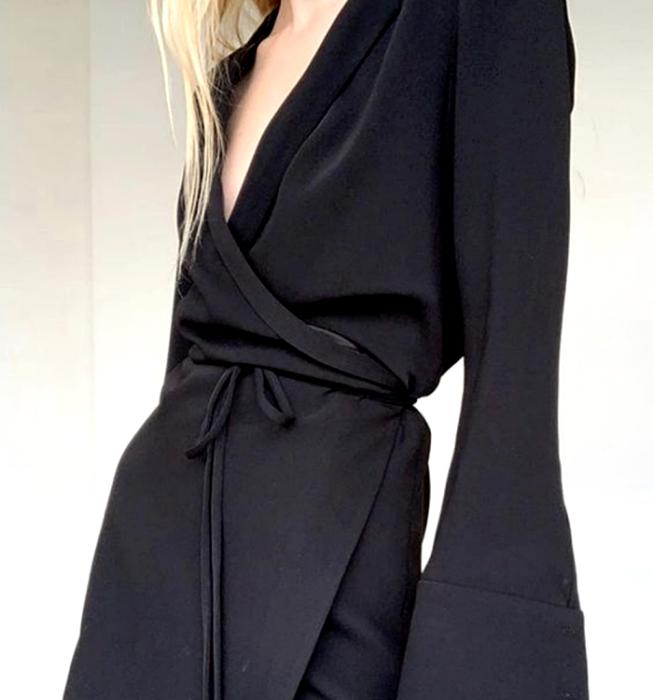 chica rubia usando un vestido negro de cuello en V, ajustado a la cintura con mangas largas estilo traje