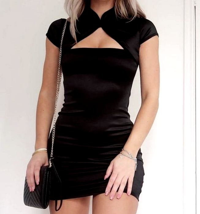chica rubia usando un vestido negro de terciopelo con cuello alto, mangas cortas y escote triangular con bolso de mano negro