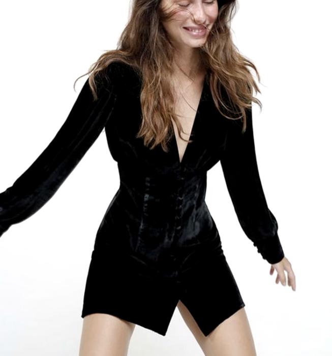 chica rubia usando un vestido negro de manga larga, cuello en V, con botones al frente