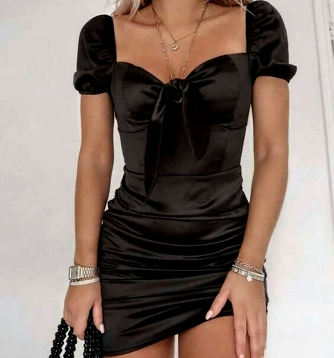 blonde girl wearing a black short-sleeved satin dress with square neckline and front bow